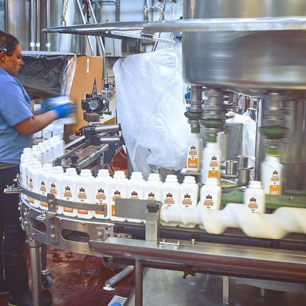 Containers, waiting to be filled with our Local Honey Kefir, are placed on the line.
