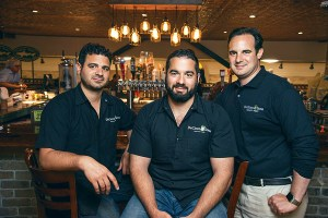 left to right: Chris DeCicco, Joseph DeCicco Jr., and John DeCicco Jr. in front of their Craft Beer Bar in Millwood