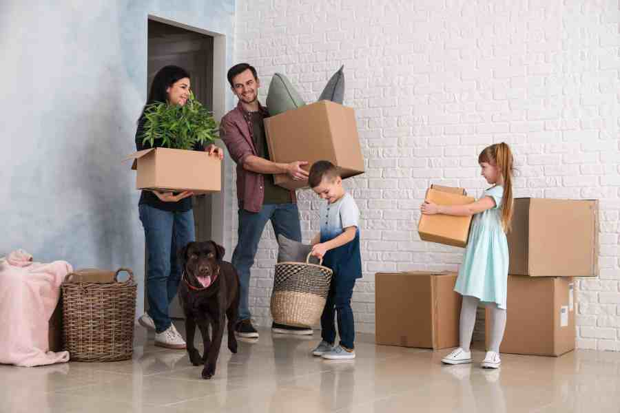 An image showing a family with their pet during their move. Mom, Dad, son, and daughter each are carrying boxes.