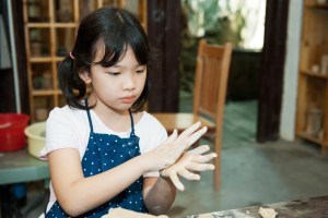 Asian kid shaping pottery