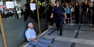 An elderly man is crying outside a national bank branch as pensioners queue to get their pensions, with a limit of 120 euros, in Thessaloniki on 3 July, 2015. Greece is almost evenly split over a crucial weekend referendum that could decide its financial fate, with a 'Yes' result possibly ahead by a whisker, the latest survey Friday showed. Prime Minister Alexis Tsipras's government is asking Greece's voters to vote 'No' to a technically phrased question asking if they are willing to accept more tough austerity conditions from international creditors in exchange for bailout funds. AFP PHOTO /Sakis Mitrolidis        (Photo credit should read SAKIS MITROLIDIS/AFP/Getty Images)