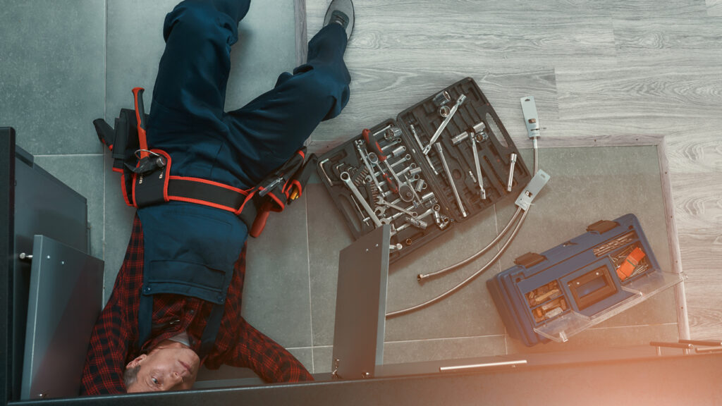 High angle view of plumber in dunwoody wearing auniform lying on floor in the kitchen and using wrench while repairing water pipe in kitchen. Toolbox on the floor. Horizontal shot