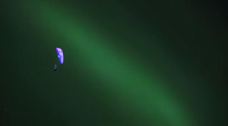Guy Paragliding Through Aurora Borealis in Norway