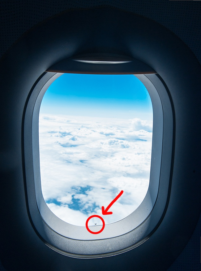 The tiny hole in the window of a plane