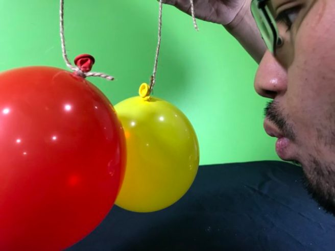 Blow em apart science experiment - blowing between the two hanging balloons