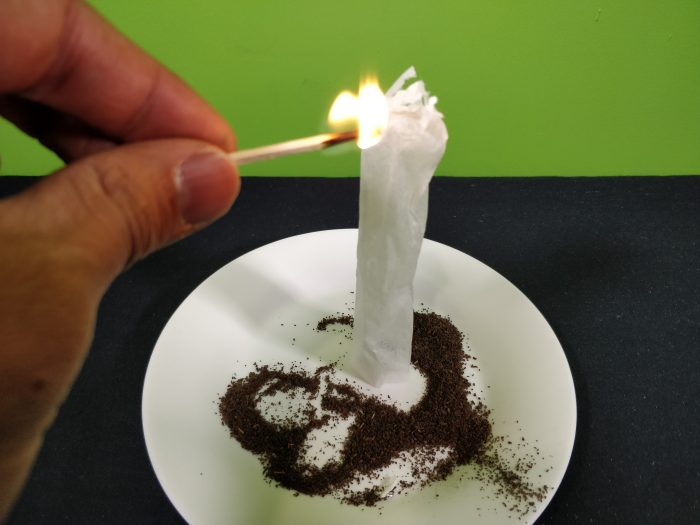 Lighting a opened tea bag cylinder with a lit match