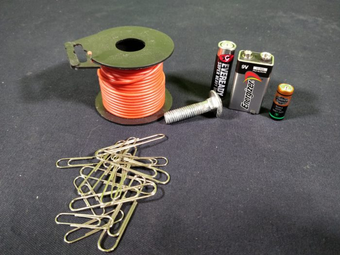 Materials needed to make an electromagnet showing a roll of insulated red wire, paper clips, a steel bolt and a variety of battery sizes
