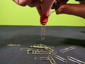 Paperclips attracted to a homemade electromagnet