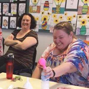 two ladys laughing while they do an experiment involving a bottle and a balloon