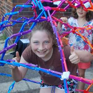 Girl inside a huge hoberman sphere during a kids science party