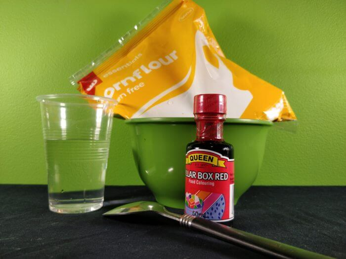 Materials to make corn flour slime showing a cup of water, a bowl, red food colouring and corn flour in a packet