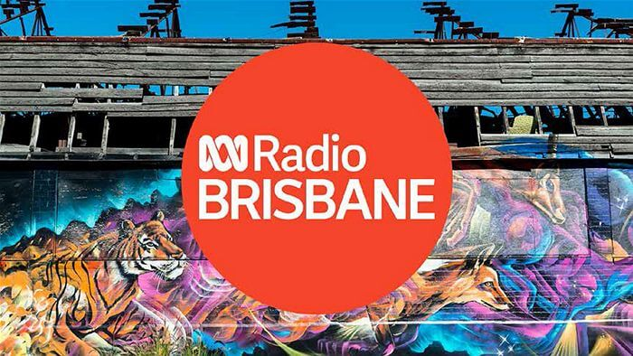 red logo with white text in the middle saying radio Brisbane with street art in the background