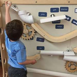 boy wearing a blue shirt putting a marble into the marble run