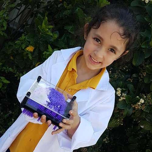 Close up of Girl in a lab coat holding a science toy