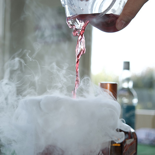 red liquid being poured out of a glass beaker into a a beaker with dry ice fog rushing out and over the table