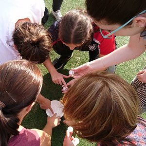 Teacher showing how to do an experiment outside to a group of kids.