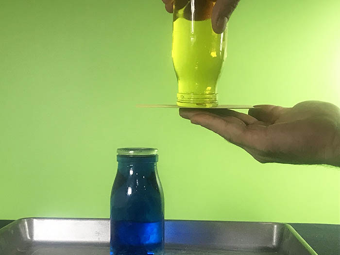 Upturned yellow water bottle with the index card underneath it being held up by a hand.
