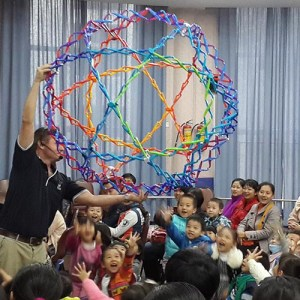 A man holding a mega hoberman sphere over very happy preschoolers during a science show
