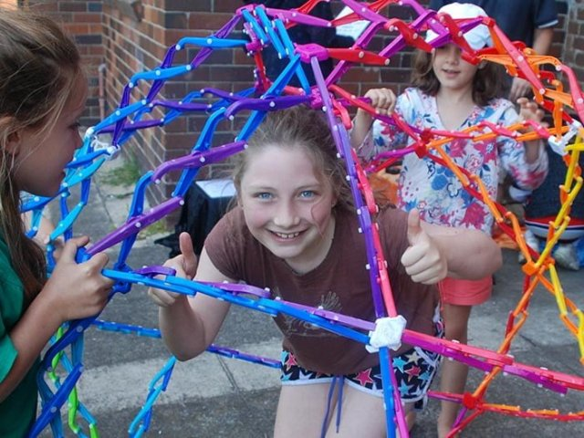 Girl inside a colourful hoberman sphere holding two thumbs up. Two smiling girls are outside the hoberman sphere holding it up.