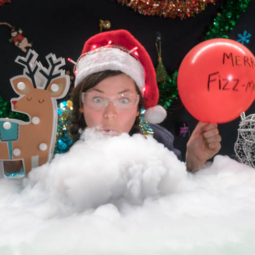 A person wearing a Christmas hat, holding a red balloon, blowing on a bowl of fog next to a reindeer
