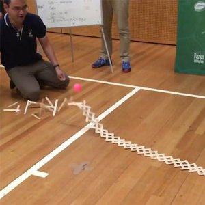 A chain of wooden tongue depressors raising up off the ground in front of a Fizzics science presenter