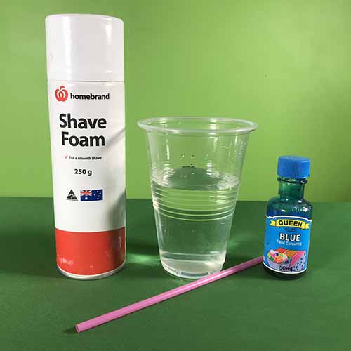 Shaving cream, a plastic cup filled with water, a pink straw and some blue food colouring