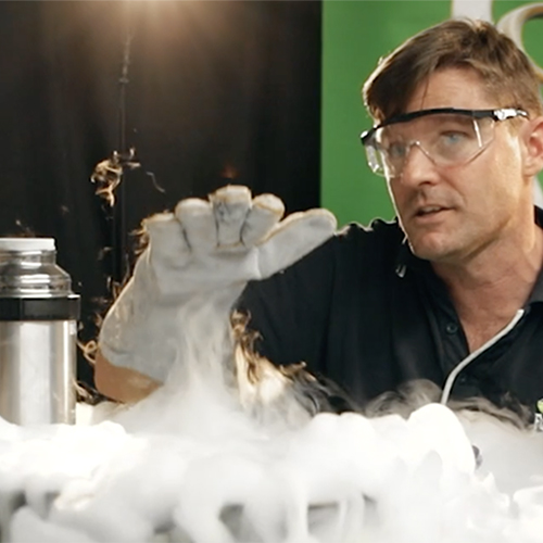 A cloud of liquid nitrogen vaur on a deask with a science presenter