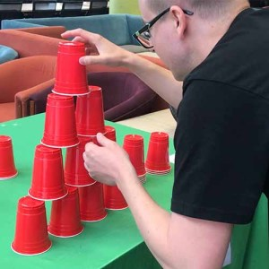 A man stacking red cups in a pyramid