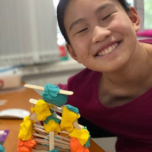 A smiling child in front of her tower creation