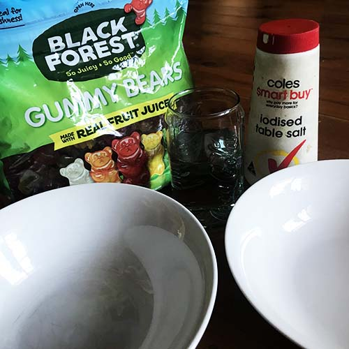 A packet of gummy bears bext two white bowls, a glass of water and a salt container