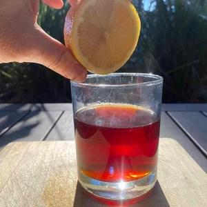 Squeezing a lemon half into a glass of tea