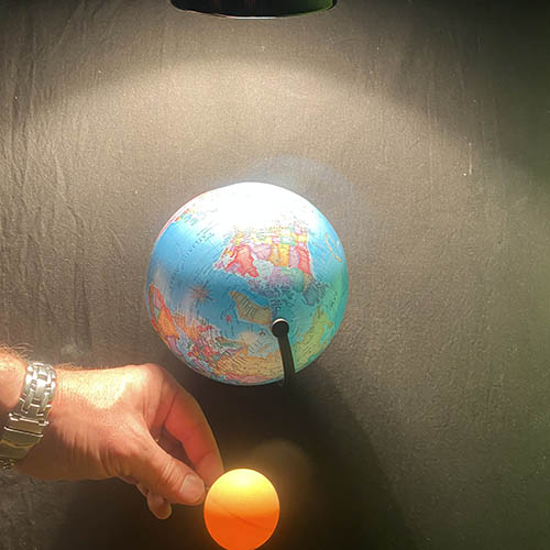 A lamp, Earth model and a ping pong ball lined up in a row. The Earth is in between the ping pong ball and the lamp