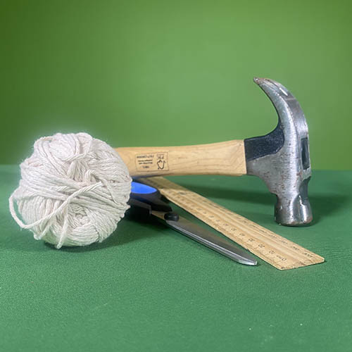 A ball of sting, hammer, scissors and a wooden ruler on a desk