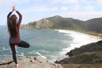 Lady doing standing balancing yoga asana near the beach
