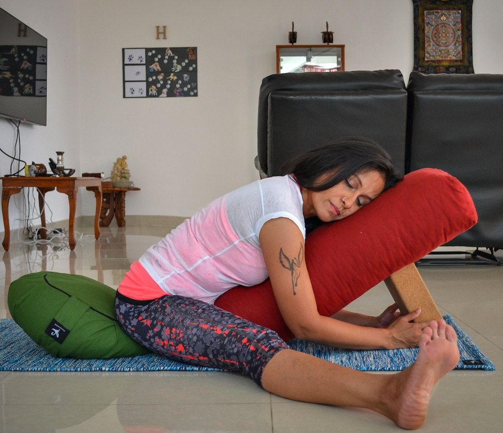 Wide legged forward fold with yoga props