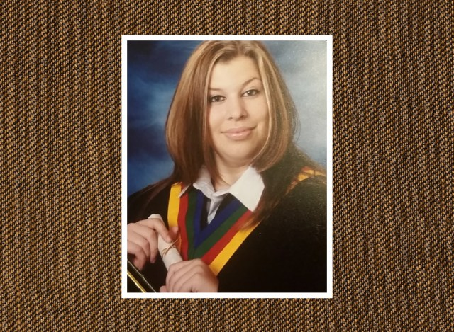 A high school grad photo of Lora. She has chunky highlights and is wearing a graduation gown and holding a diploma