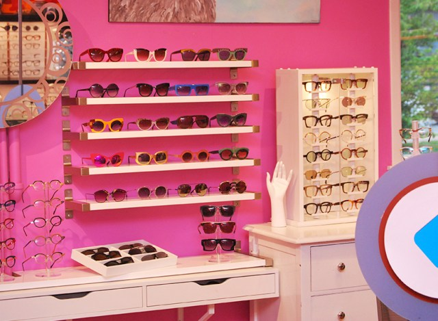 A sunglasses shop with hot pink walls, colourful sunglasses and white shelves
