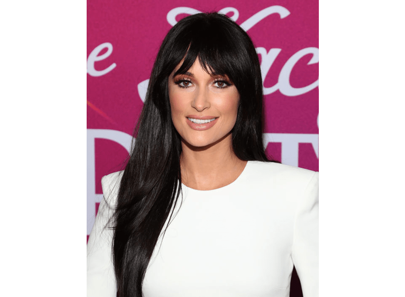 2020 hair trends: Kacey Musgraves in a white dress with long, dark hair and bangs.