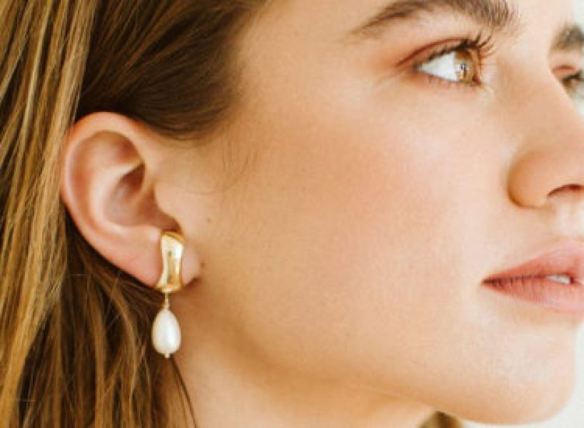 Someone faces to the side wearing a gold and pearl earring.