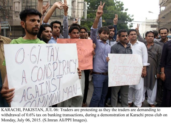 KARACHI, PAKISTAN, JUL 06: Traders are protesting as they the traders are demanding to  withdrawal of 0.6% tax on banking transactions, during a demonstration at Karachi press club on  Monday, July 06, 2015. (S.Imran Ali/PPI Images).