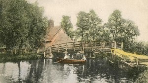 Tinted postcard showing Edwardians at leisure rowing under Flatford Bridge after 1906