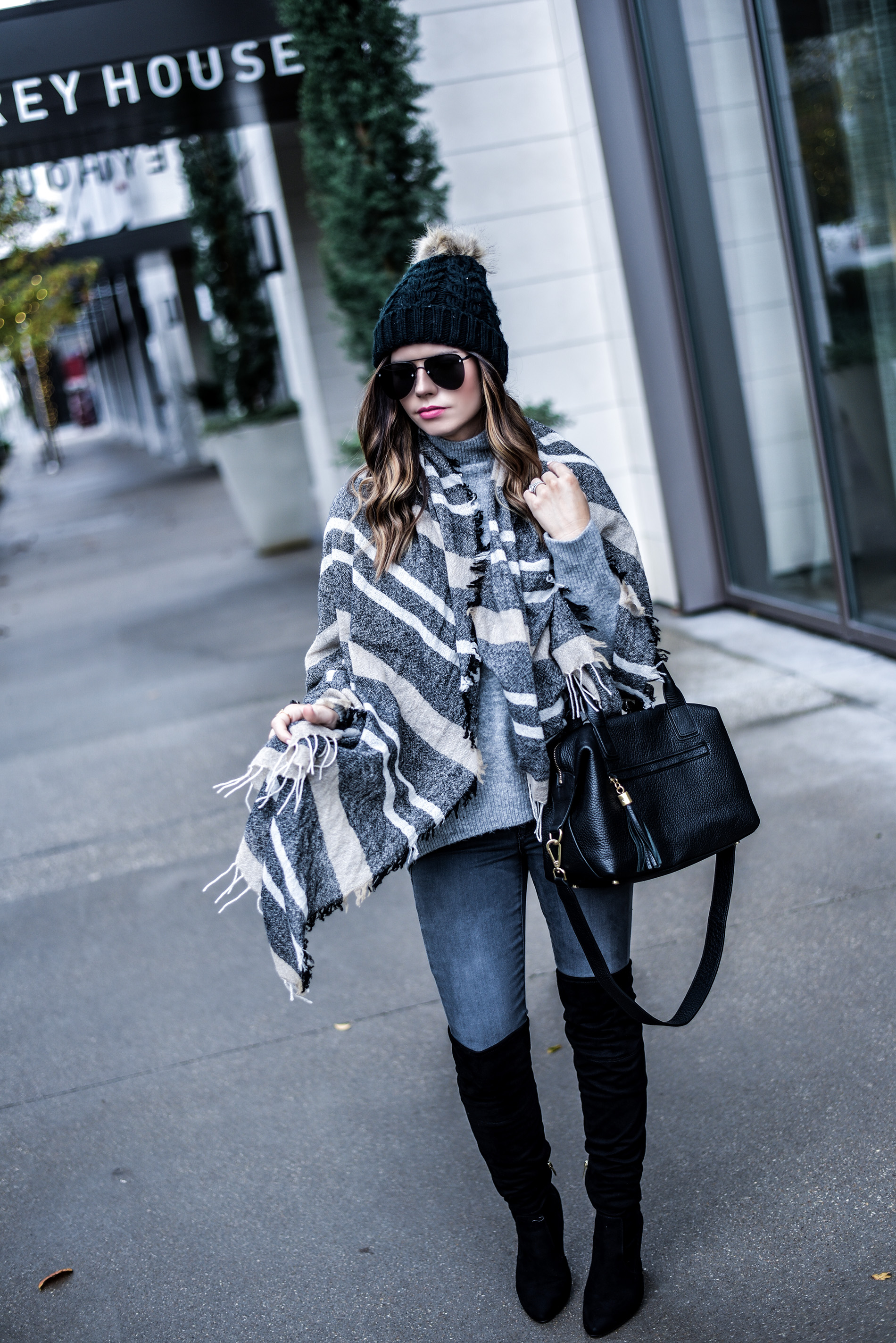 Houston fashion blogger Tiffany Jais wearing dark grey skinny jeans with Ivanka trump black over the knee boots, and a made well scarf | Women's fashion