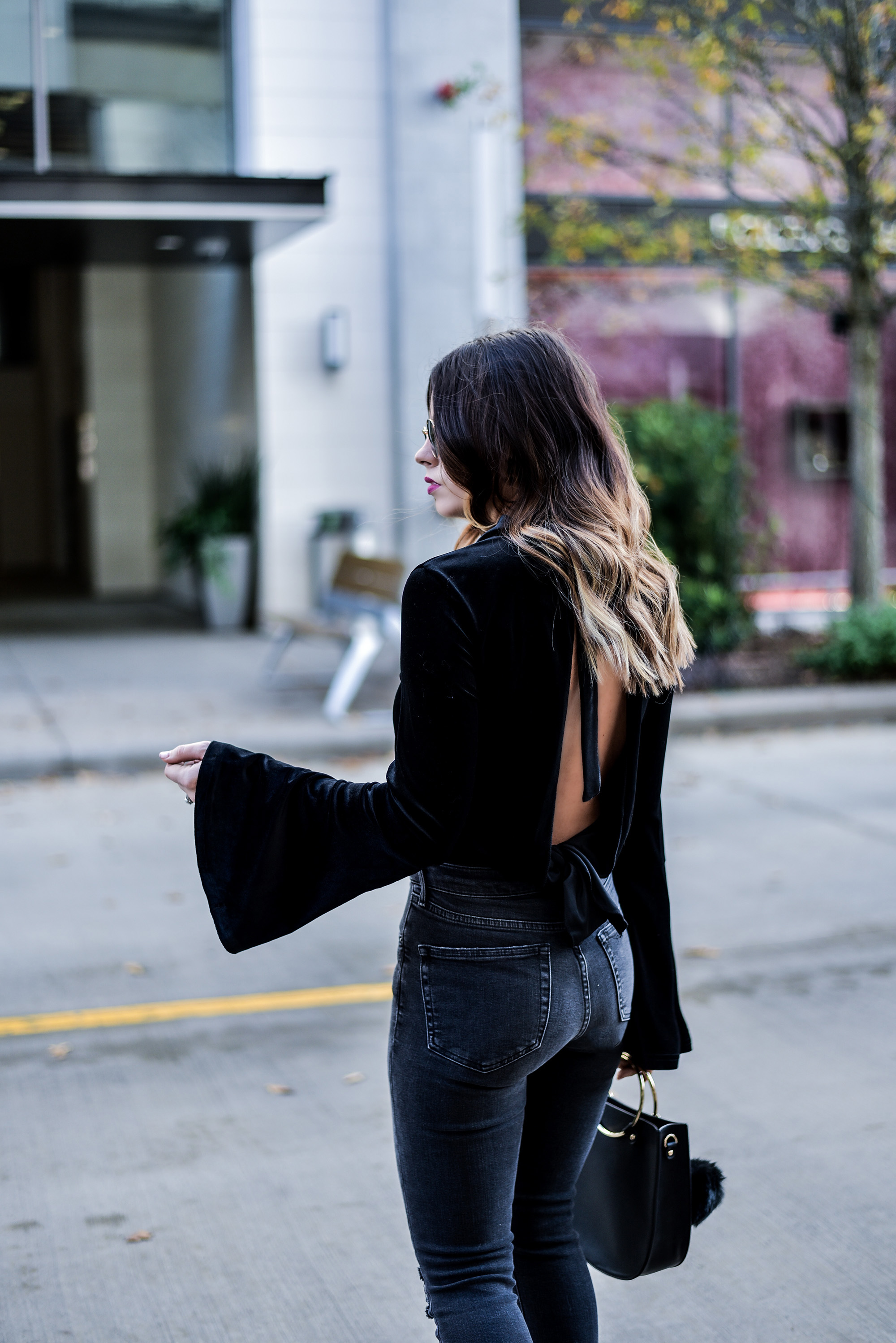 Houston style blogger Tiffany Jais wearing a bell sleeve velvet top by NA-KD, and dark grey distressed jeans from Topshop |