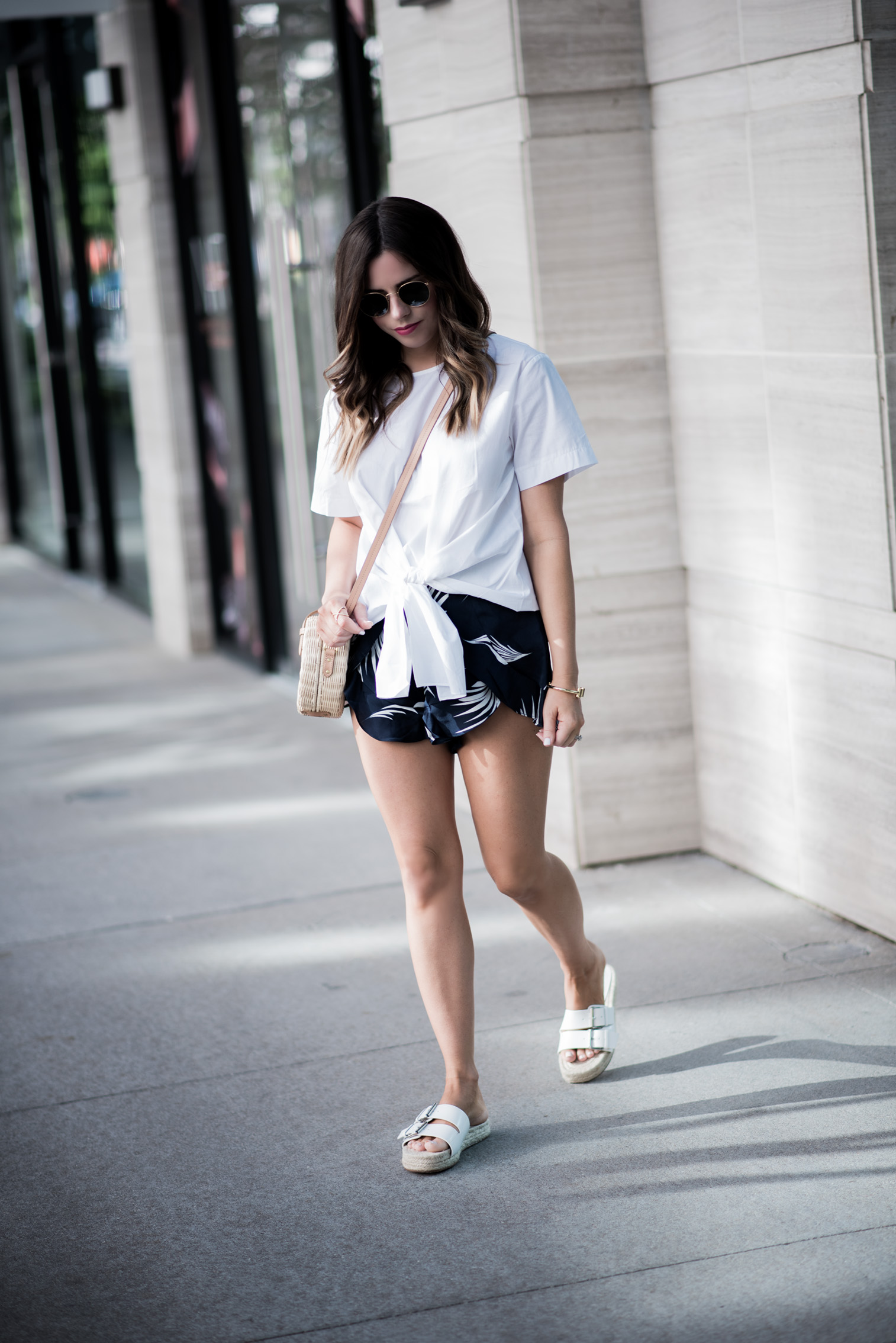 Tiffany Jais Houston fashion and lifestyle blogger | JOA front tie top, white slides, palm printed shorts, casual summer outfit, round rattan straw bag,