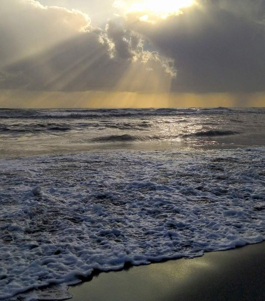 sun rays filtering through the clouds on the sea
