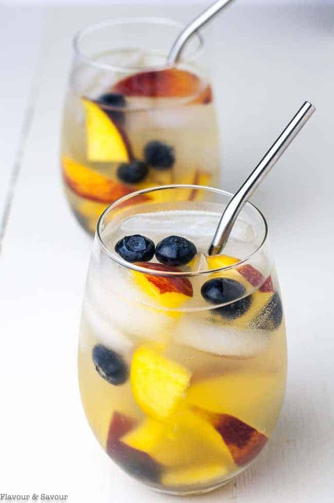 Two glasses of Peach Sangria with peaches and blueberries.