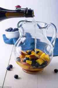 Pouring Prosecco to make Peach Sangria