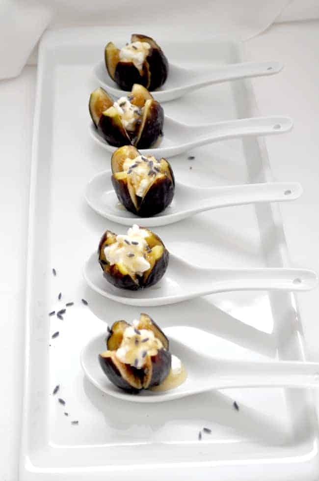 Fresh figs with goat cheese and honey in white ceramic serving spoons