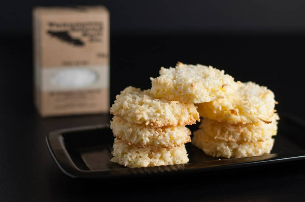 Crispy Salted Coconut Cookies with sea salt. Cookies stacked on a tray with a box of Vancouver Island Sea Salt in the background.