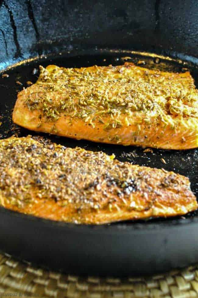 Fennel Crusted Salmon in a cast iron skillet close up view
